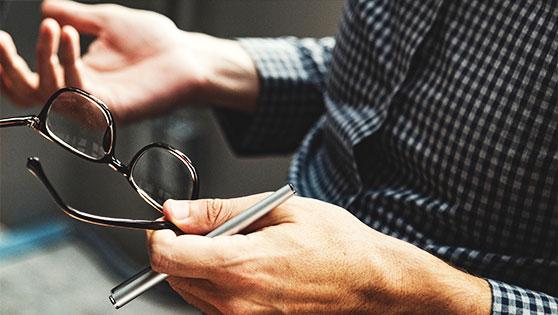 Pessoa segurando uma caneta e um óculos, ilustrando pensamento estratégico