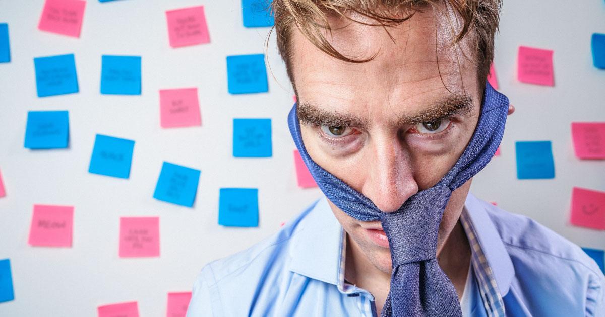 A imagem ilustra um empresário estressado e decepcionado. Ao fundo, um quadro branco com diversos post its.