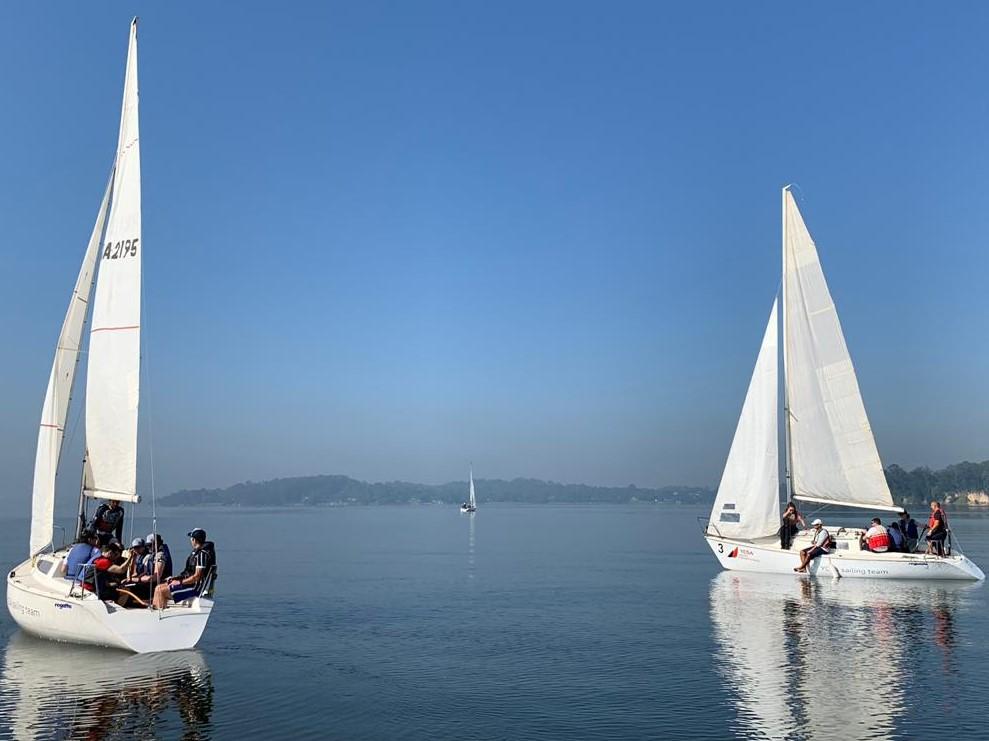 Pessoas a bordo de veleiros, ilustrando as lições do mundo náutico para trabalho em equipe e liderança de empresas